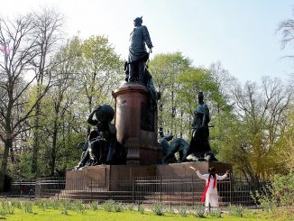 you can see a monument and and artist with a white dress and a red scarf