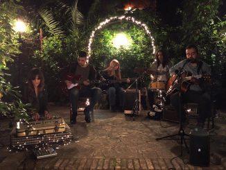 la band Portnoy sta suonando in un giardino illuminato da tante piccole luci da esterno