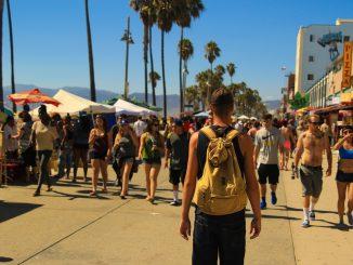una folla di persone statunitensi che cammina in gruppo ma non indossa la mascherina