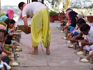 The photo represents an Indian man dressed in white and yellow providing food to a couple of parallel lines of people. The meal consist of a dish with some rice and a iron glass of water