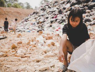 Emergenze permanenti: fame nel mondo, bambina asiatica fruga in discarica
