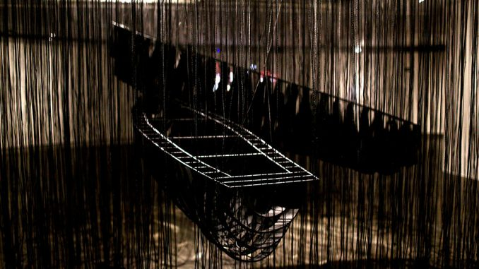 installation by the japanese artist Chiharu Shiota wirh two boats and many black ropes around them