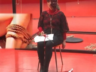 Bondage art, performance by Vitaldo Conte, girl tied to a chair, red background