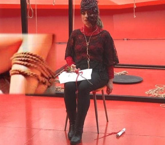 Arte Bondage, foto di performance artistica con donna legata su sedia, sfondo rosso