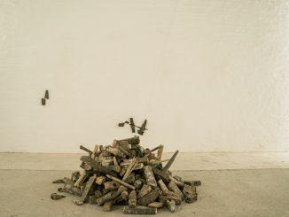 Utensili in legno, manici e teste di martelli raccolti in un mucchietto su un pavimento di mattonelle grigio chiaro, vicino a una parete bianca
