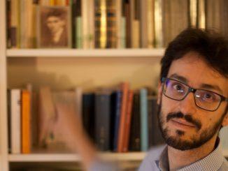 nella foto, sulla destra, si vede il volto di un giovane scrittore con la barba, i baffi e gli occhiali neri; ha gli occhi neri. Sullo sfondo una libreria bianca.