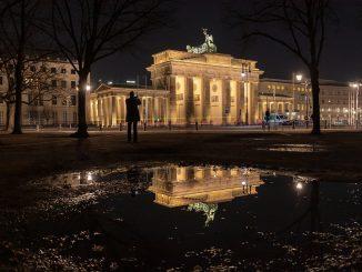 in uno spazio urbano di notte una persona fotografa un monumento illuminato e riflesso in una pozzanghera