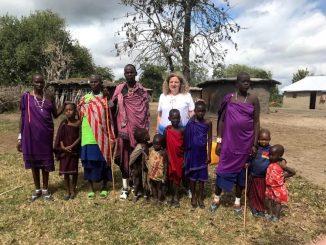 gruppo di persone di colore di varie età in mezzo alla natura. In mezzo a loro una donna bianca con i capellli biondi