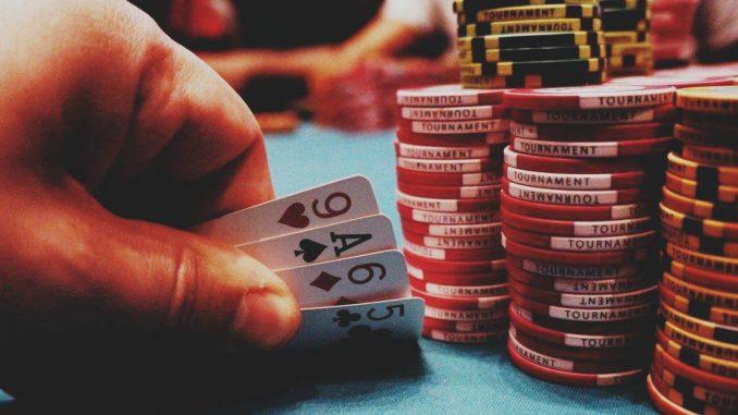 Nella foto: un tavolo da gioco, una mano che tiene quattro carte in mano, molte fiches