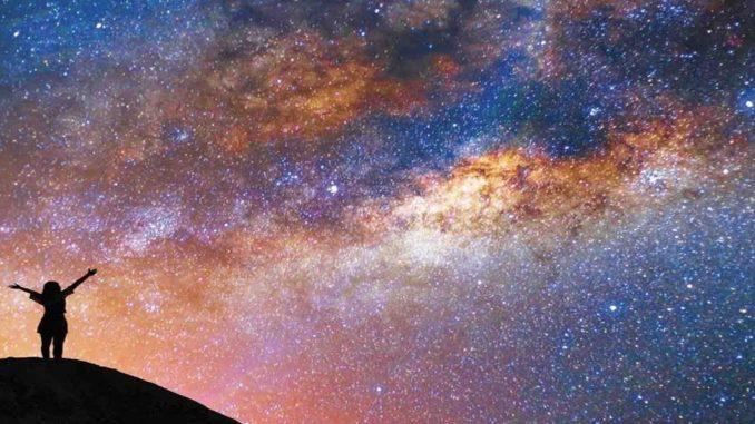 cielo stellato invaso in buona parte da una luce gialla. In controluce sagoma di una persona in piedi con le braccia spalancate verso il cielo