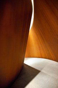 nella foto a colori si vede in primo piano una scultura in legno illuminata dalla luce, con, al centro, un passaggio