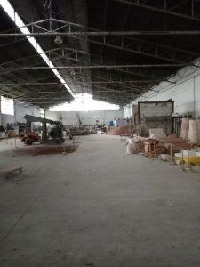nella foto si vede un capannone industriale dismesso con scatoloni a terra e macchinari in disuso.