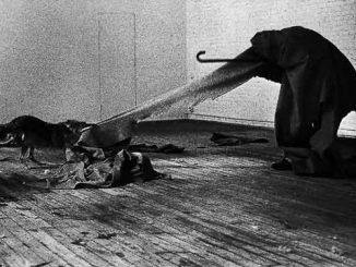 Foto in bianco e nero: un uomo ricoperto con pesante drappo si stoffa, il capo non visibile, che tende ad un animale simile ad un cane della stoffa.