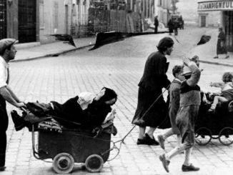 Foto degli anni 40 che ritrae gente in strada che cammina spingendo carrozzine contenenti anziani e bambini.