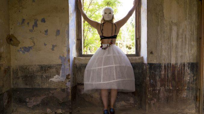 Marilena Vita artista italiana con fotografia di donna in gonna davanti a finestra abbandonata