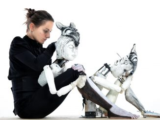 Photograph of the performer Marta Cuscunà sitting on the ground with her puppets