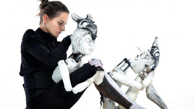 Fotografia della performer Marta Cuscunà seduta a terra con i suoi pupazzi.