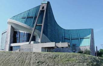 struttura architettonica dall'aspetto moderno, presumibilmente una chiesa, si staglia contro il cielo azzurro