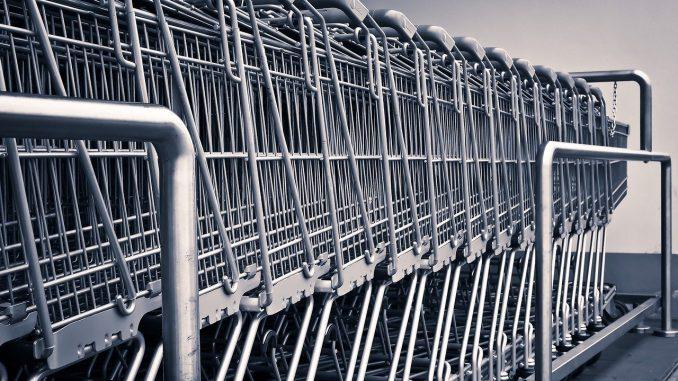 foto in scala di grigi di un fila di carrelli del supermercato