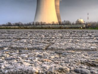 The picture is a photography that represent a huge chimney in the middle of a clear blue sky. the framing of the picture allows us to see a big chunk of the grey asphalt and all its roughness