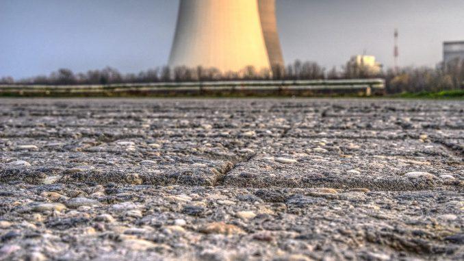L'immagine è una foto che ritrae l'enorme ciminiera di una centrale in un cielo terso. La ciminiera è ripresa a livello del terreno, occupato da un asfalto di cui si vedono le crepe e le asperità in maniera ravvicinata