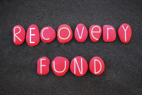 The picture represent the Recovery Fund sign. Each one of the white letters is in the center of a red stone and all the stones are on a dark concrete-like surface
