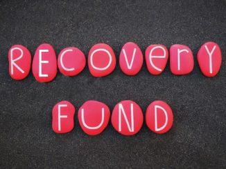 L'immagine mostra la scritta Recovery Fund in bianco. ciascuna lettera è all'interno di un ciottolo rosso ed i ciottoli sono disposti su una superficie scura simile ad asfalto