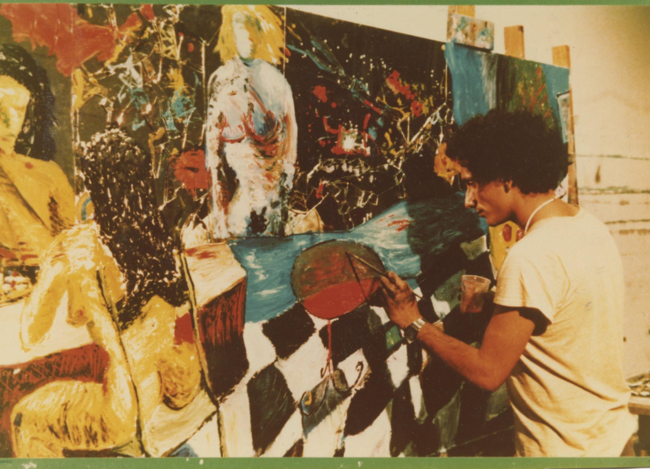 l'immagine mostra l'artista Bedri Baykam intento a dipingere. L'artista si trova nella parte destra della foto mentre il lato opposto è occupato dalla grande tela a cui sta lavorando