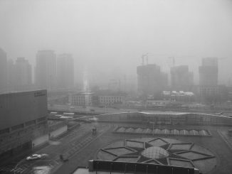 black and white photo of a city enveloped in fog