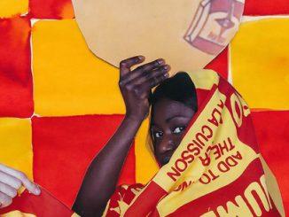 ragazza di colore avvolta da una coperta con colori e scritte rosse e gialle; col braccio destro sorregge un oggetto dalla forma sferica
