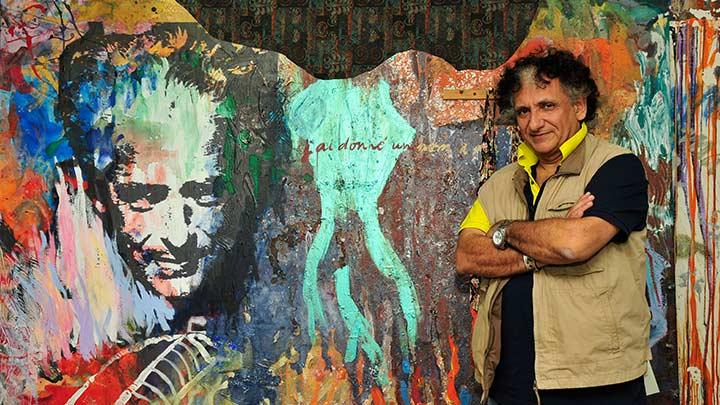 L'immagine mostra l'artista Baykam davanti ad un suo murales