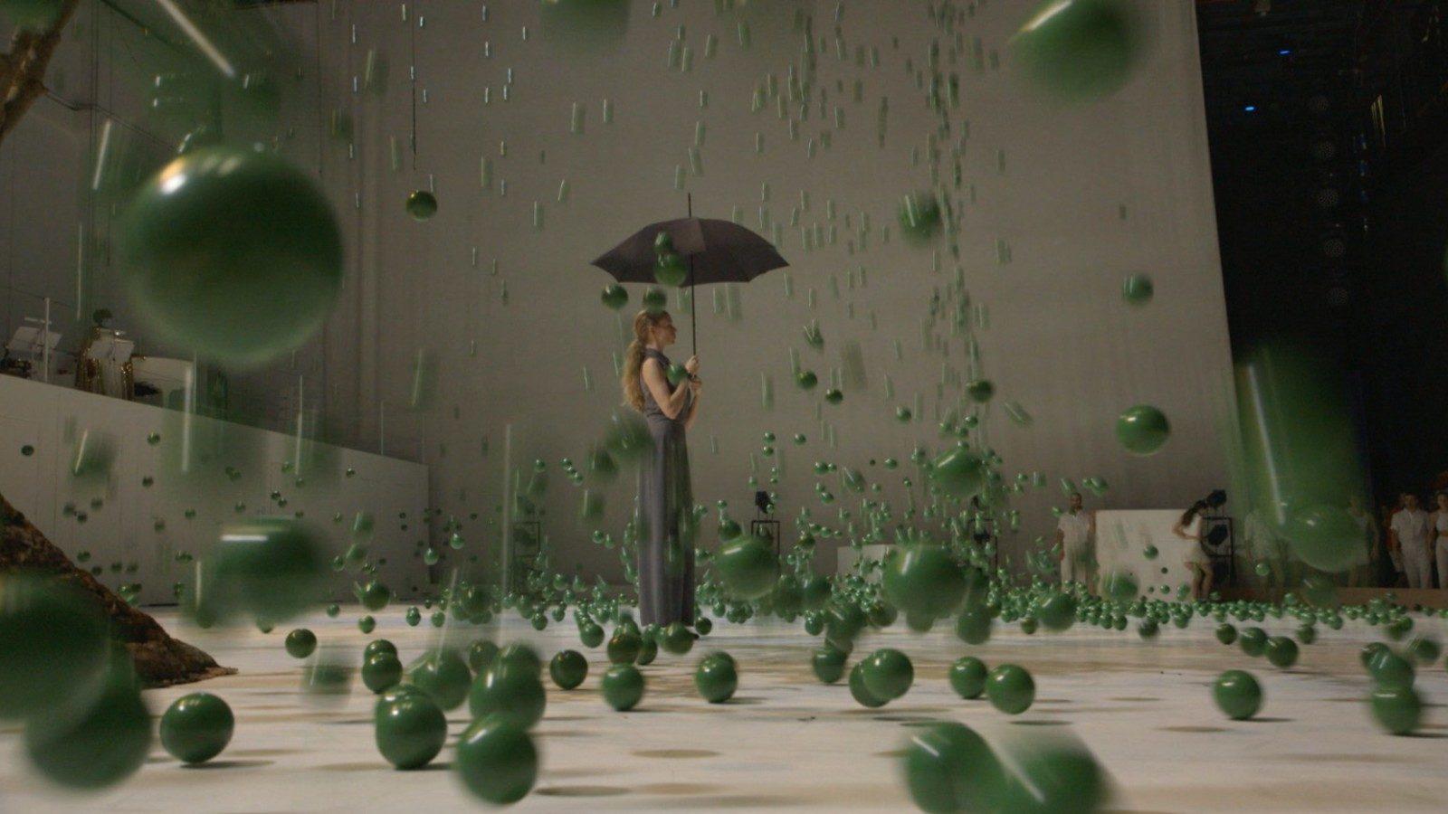 Alexander Ekman choreographer from Sweden, scene of his ballet, ballerina with umbrella, raining green balls