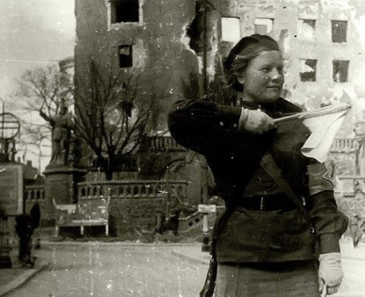 in this black and white photo you can see on the right a young woman, an auxiliary of the Red Army; she puts in her hand a flag.
