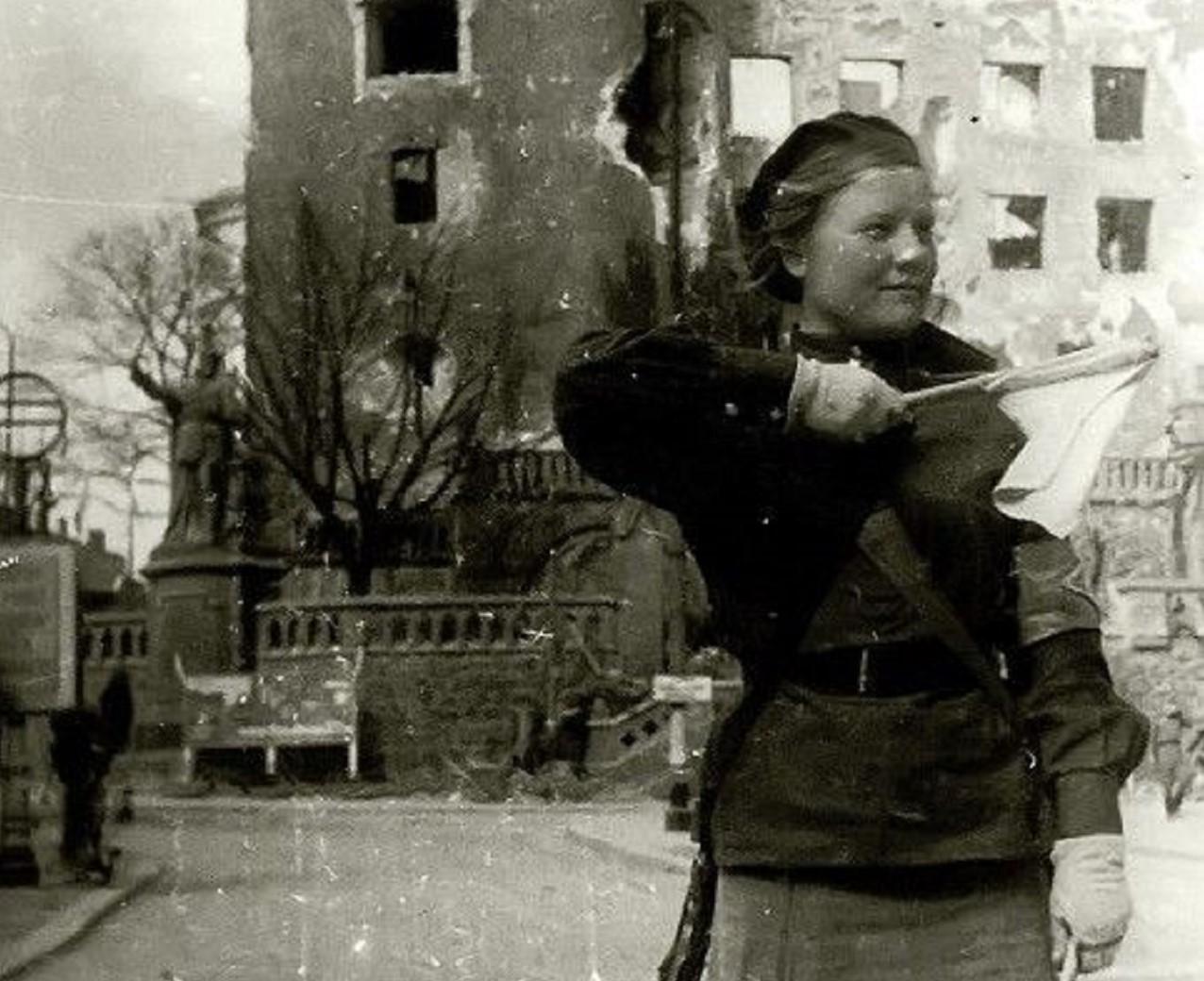 nella foto in bianco e nero si vede, in primo piano sulla destra, una donna, che è un'ausiliaria dell'Armata Rossa, con in mano una specie di bandiera.