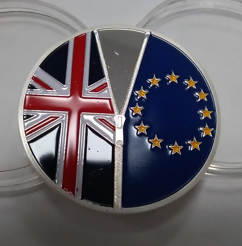 l'immagine mostra una medaglia metallica su cui sono incise le bandiere della union jack a sinistra e quela dell'Unione europea a destra, come se fossero du lati di una maglia, separata da una zip (anch'essa incisa)