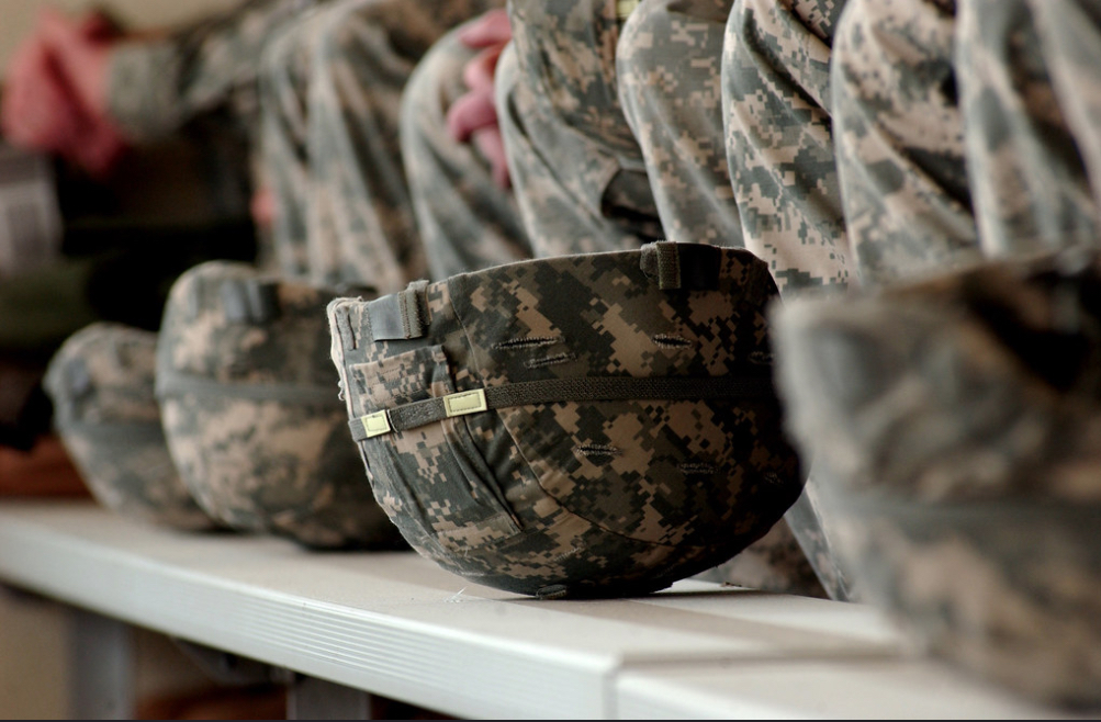 in the color photo you can see many soldiers' helmets lined up with the typical colors of the military style, and, behind them, the uniforms of the soldiers.