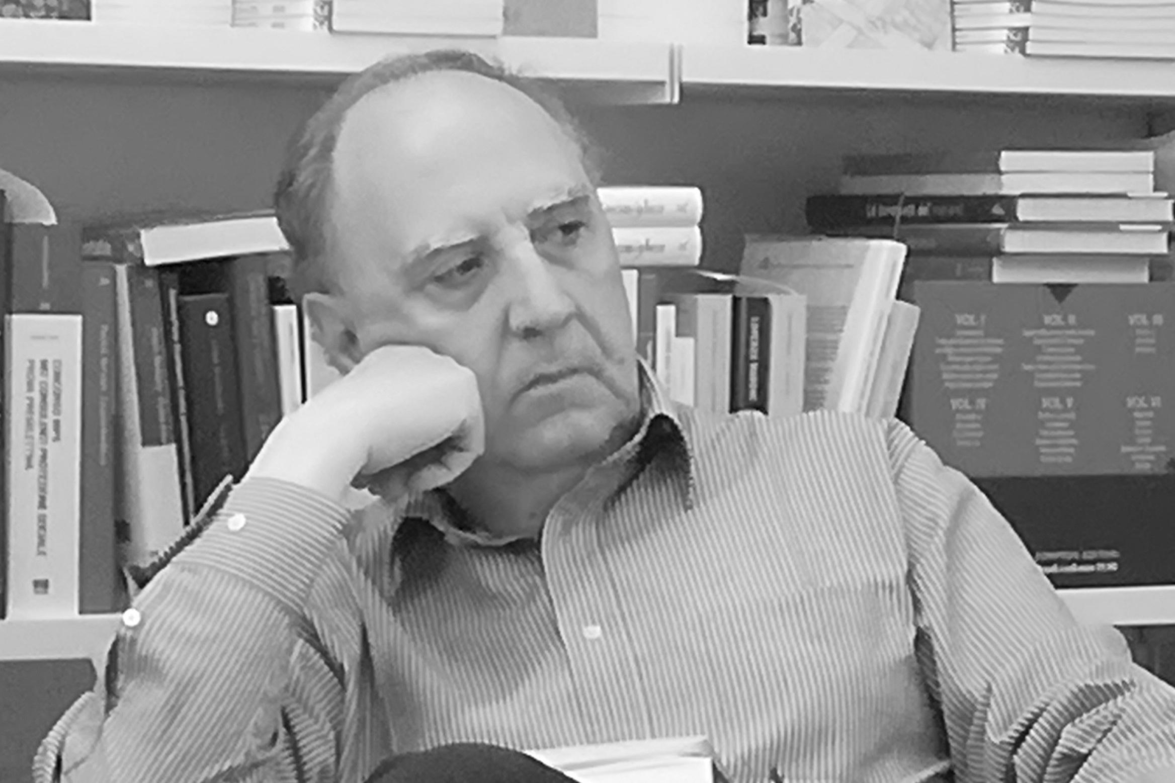 nella foto in bianco e nero si vede un uomo anziano che indossa una camicia a righe, con la mano destra poggiata sulla guancia destra