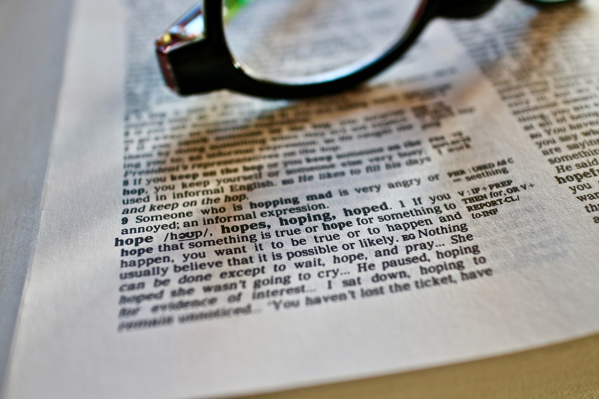 in the color photo you can see an English newspaper and above it a pair of black-rimmed glasses