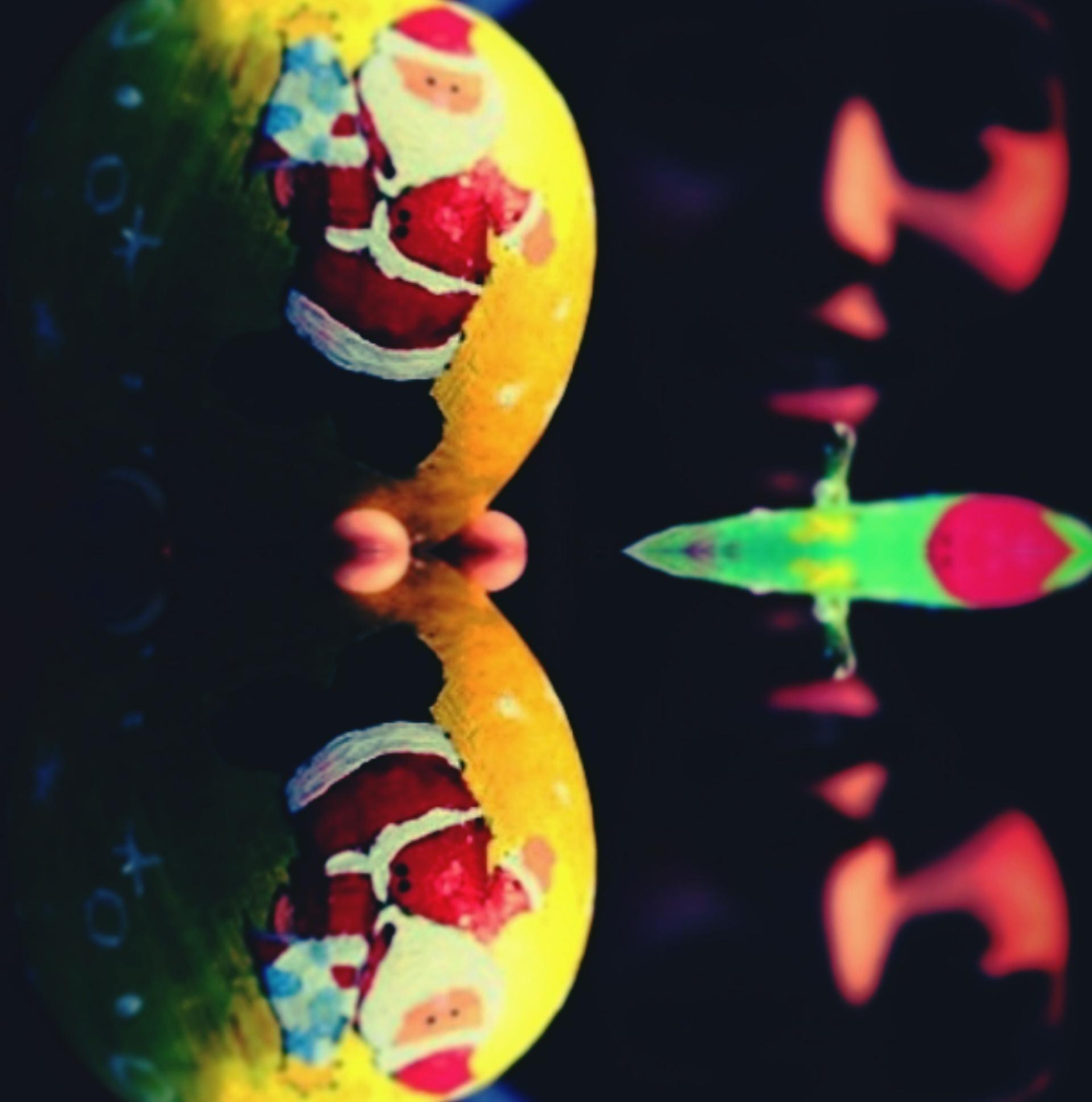 L'immagine mostra una pallina dell'albero di natale gialla con un babbo natale disegnato con tratti elementari. La pallina è riflessa su una superficie scura, i cui contorni si confondono con quelli dello sfondo