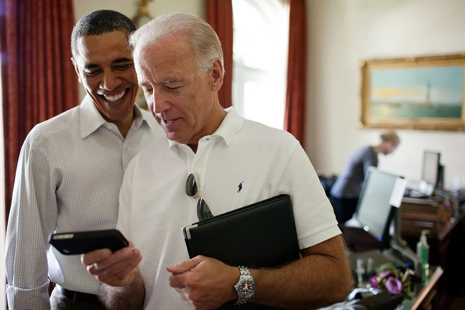 in the colored photo you can see two men, Barack Obama and Joe Biden. Biden wears glasses on the shirt and puts in his hands a tablet and a tape recorder.