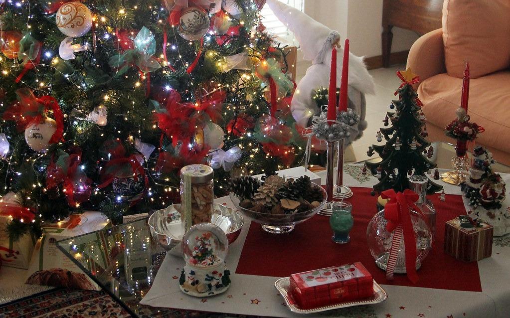 nella fotografia: un albero di Natale, candele rosse, soprammobili natalizi, cioccolatini, pacchetti dono, pigne, sono i simboli del Natale italiano.