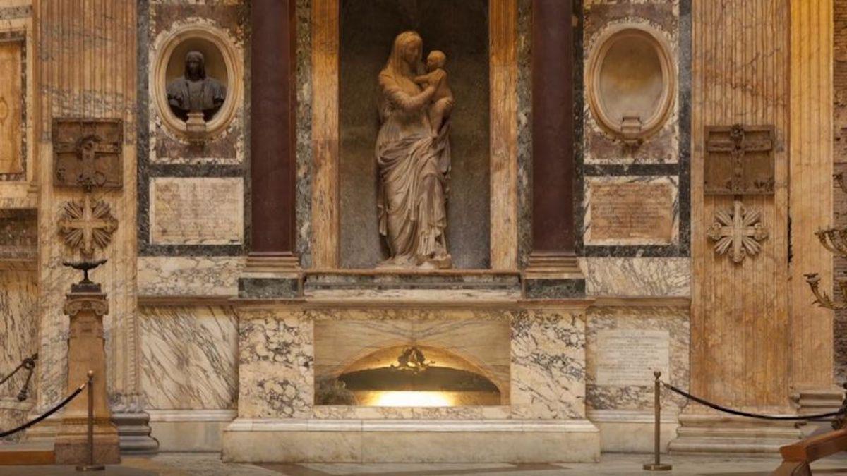 fotografia della tomba marmorea di Raffaello Sanzio in Roma al Pantheon sormontata la scultura in marmo chiaro de La Madonna del Sasso opera di Lorenzetto allievo del maestro