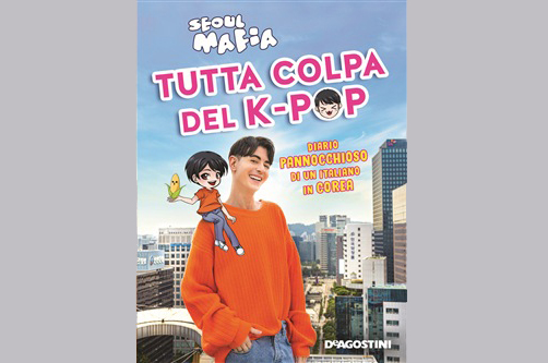 "The picture (on a grey background) shows the cover of the book ""Tutta colpa del K-pop. Diario pannocchioso di un italiano in Corea"" by Seoul Mafia. The autor is in the center of the picture, wearing an orange shirt. The South Korean capital, Seoul is on the background while the title and a manga-version of the author are over the picture"