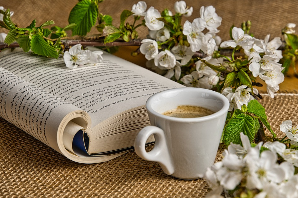 in the color photo you can see a cup with coffee inside, an open book and a branch of white flowers on a table