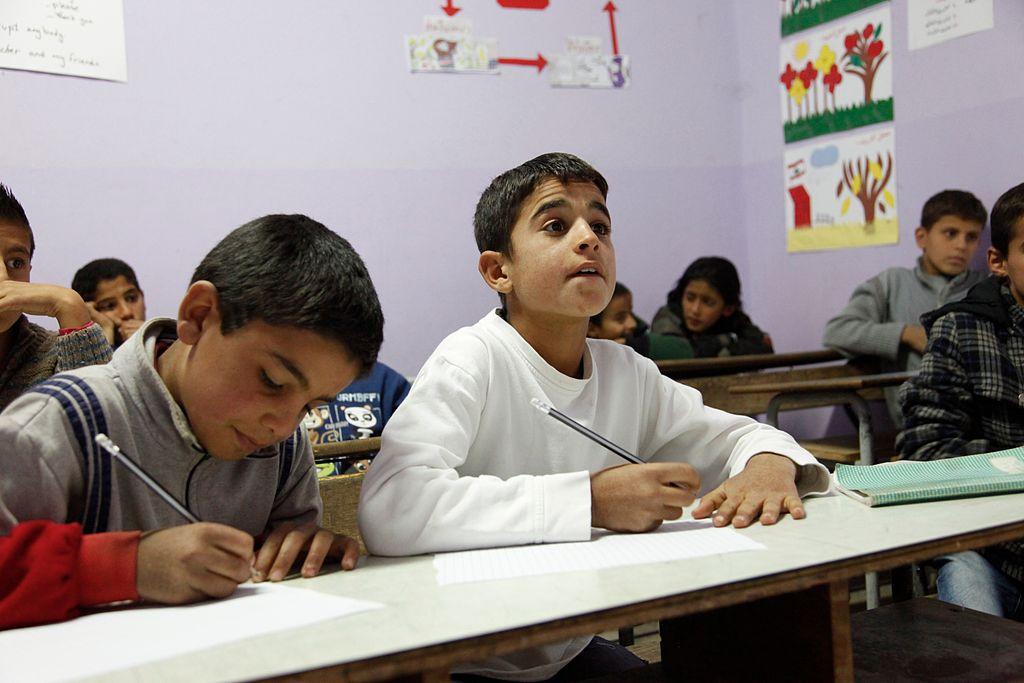 in questa foto a colori si vedono alcuni bambini sui banchi di scuola