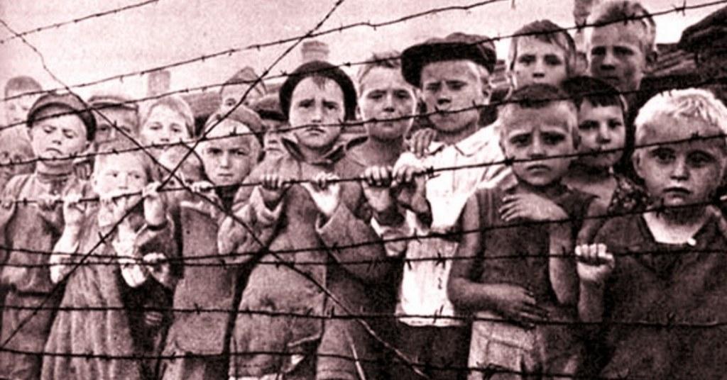 nell'immagine in bianco e nero si vedono bambini rinchiusi in un campo di concentramento nazista, che si appoggiano a un filo spinato