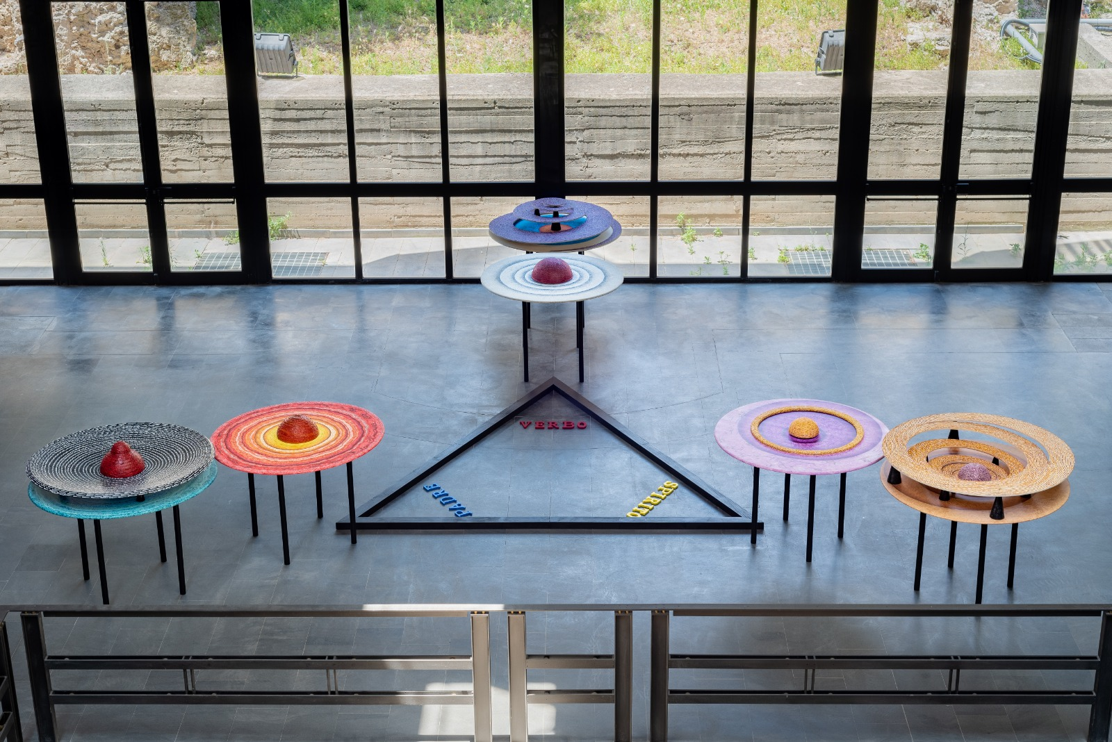 Unpublished visual of the artist Rosario Genovese composed of six tables with different colors and materials placed at the top of a triangle, on the ground, with a black perimeter, inside whose vertices there are the words verb, mother, spirit.