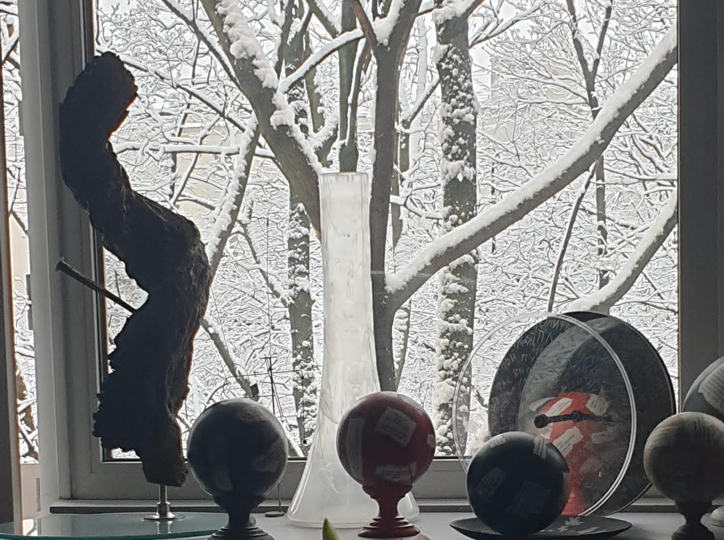 nella foto a colori si vedono alcune palle colorate con una base di legno, un vaso bianco trasparente, tutti poggiati sul davanzale di una finestra che si affaccia su uno spazio esterno innevato