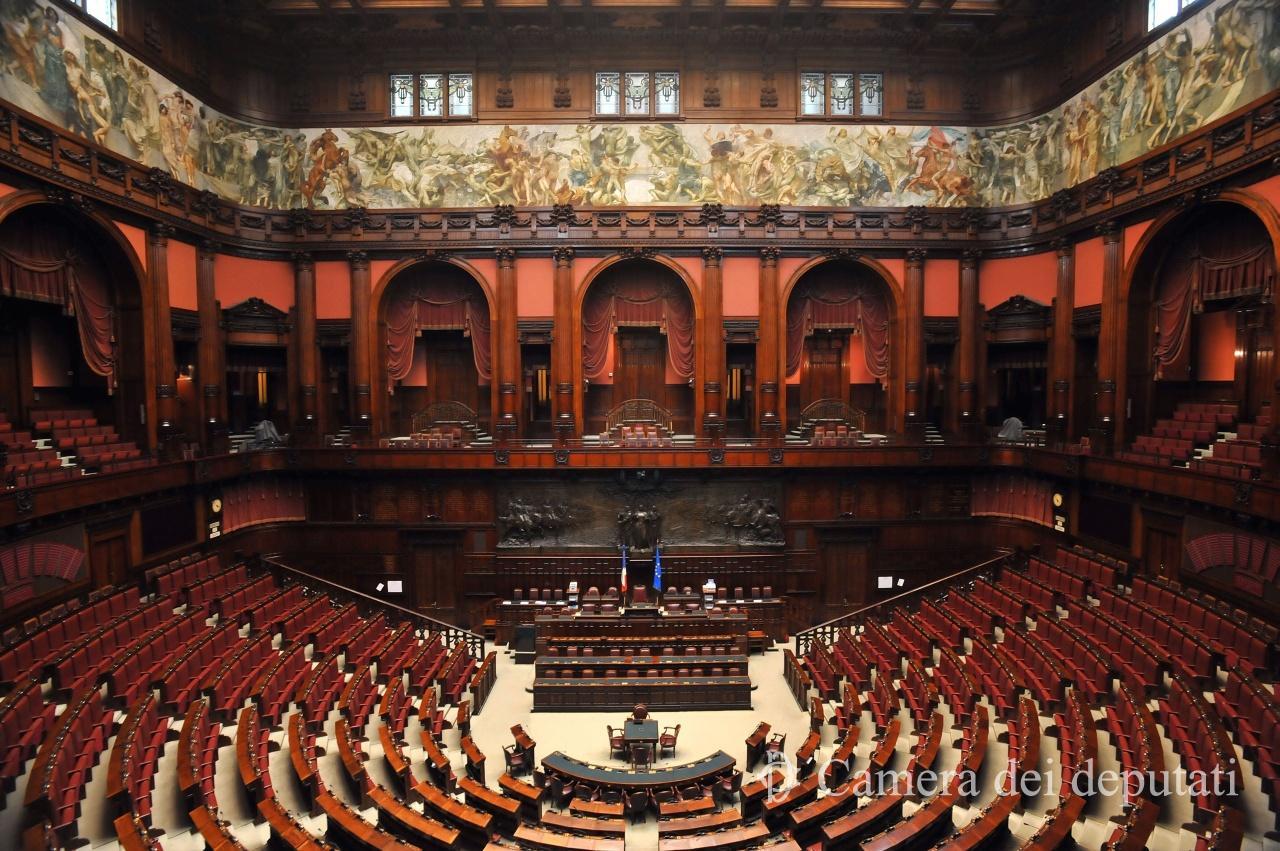 nella foto a colori si vede l'emiciclo della Camera dei Deputati, con, al centro, la postazione in cui siede il presidente della Camera.