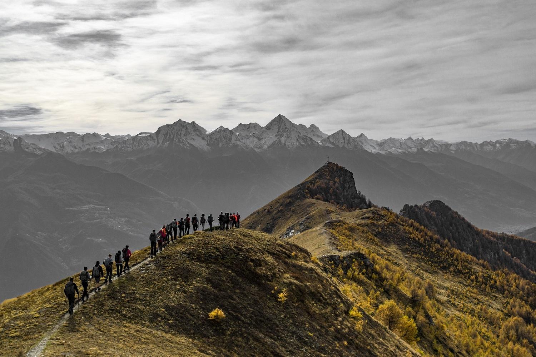 su un sentiero di montagna un gruppo di persone cammina in fila indiana